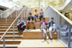 University students sit on stairs with laptops looking happ