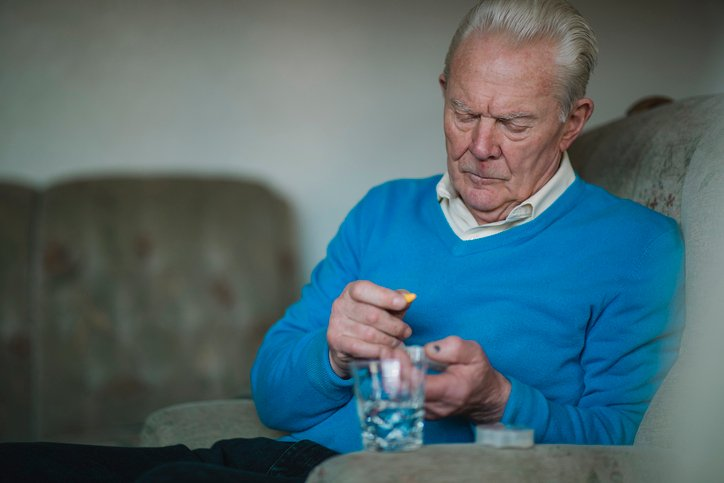 An elderly man sits on the sofa and organises his pills